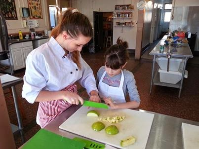 Sandra showing little girl how to slice and chop apples